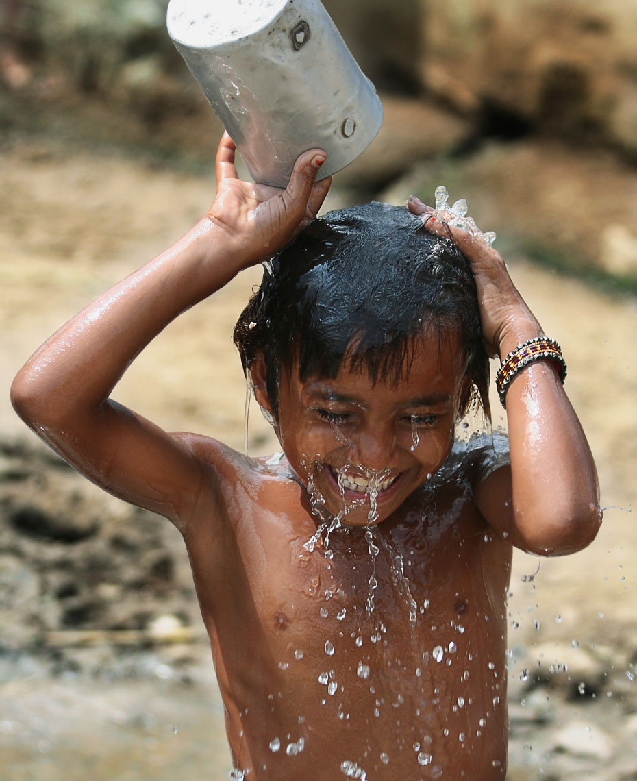 indian-boy-dumping-pale-of-water.jpg